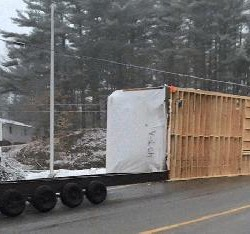 Modular home slides off trailer on Gorham rotary during rush hour