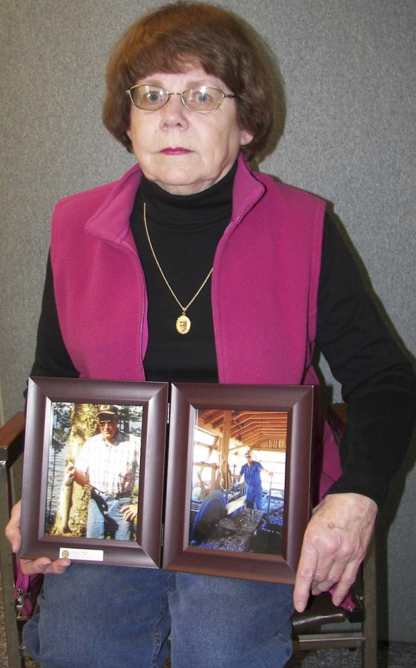 Barbara Smith of Woodland holds two photographs of her late husband, Darrel, whose murder remains unsolved.