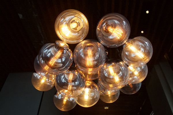 Clustered lights in a chandelier shine on a table at UNION, the Press Hotel's restaurant in Portland. UNION is one of the city's many eateries setting itself apart not only by its cuisine but by its design as well.