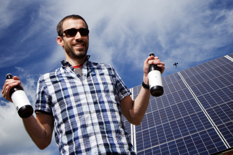 Jeremy Lindberg of Maine Beer Company in Freeport stands in front of a new solar array at the brewery in June 2015. The company's roof is also covered with the power-generating panels.