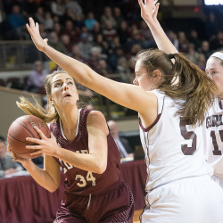 Edward Little's Jordyn Reynolds looks to the basket past Gorham's Mackenzie Holmes and Kristen Curley (15) at Saturday night's  Class AA girls basketball state championship at the Cross Insurance Arena in Portland.