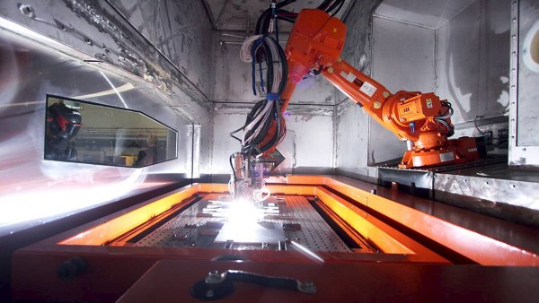 A worker operates one of the large-scale 3D printers developed by Norsk Titanium AS in Norway in this undated handout photo obtained by Reuters July 25, 2015.