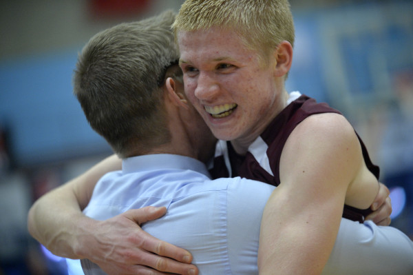 Maxwell Mattson hugs his father, assistant coach Matthew Mattson after George Stevens Academy won the Class C state championship Saturday night at the Augusta Civic Center. This was the first championship for the boys team since 2003.