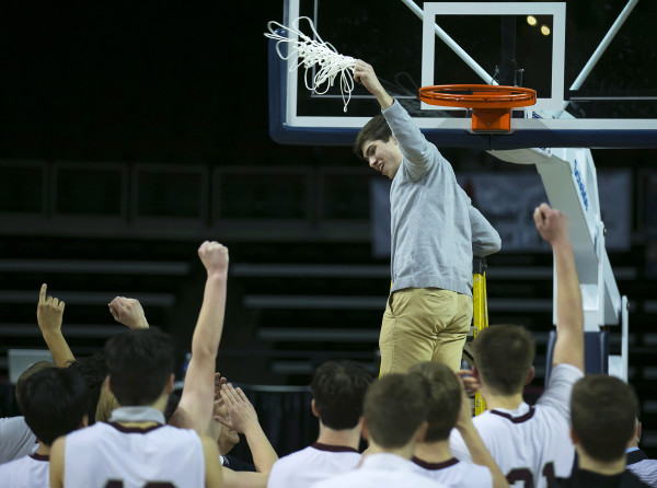 George Stevens Academy's William Entwisle (center) swings the net around his head after defeating Bucksport during the Class C North boys championship basketball game at the Cross Insurance Center in Bangor Saturday night.