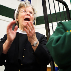 Sister Edward Mary Kelleher cheers on the Catherine McAuley High School basketball team on Friday night in Portland. The team dedicated their season to Kelleher, who headed the all-girl school for 30 years.