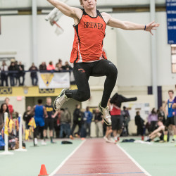 Brewer's Erick Seekins gets a lot of height during his long jump at the Class A boys state track championships Monday at the University of Southern Maine in Gorham. He won the event with a distance of 21 feet, 2 inches.