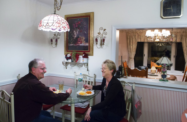 Tom Picard (left) laughs with his wife, Tammy Shorey Picard, during dinner late Sunday evening at their home in Millinocket before Tom makes the trip to his apartment in Winslow to work in the Huhtamaki plant in Waterville for the week. He says he lives &quotthe new normal.&quot As a millworker, Tom has been laid off 10 times since 1980. Now, with home prices in the dumpster in his hometown of Millinocket, he can't sell his nearly paid off home for fair value, so he commutes to his new job 130 miles away, at the Huhtamaki plant in Waterville.