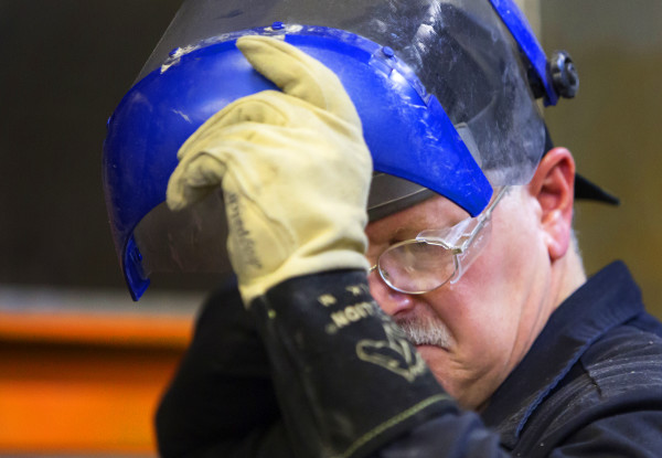 Tom Picard checks his weld during his 12-hour shift at the Huhtamaki plant in Waterville. Picard says he lives &quotthe new normal.&quot As a millworker, he has been laid off 10 times since 1980.