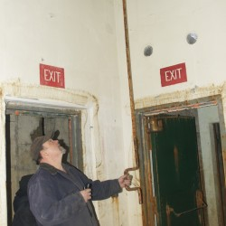 Dave Prentiss demonstrates the hand crank once used to open and close the air ducts leading into the former Nike missile silo on his Limestone property.