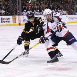 Washington Capitals right wing Justin Williams (right) controls the puck from Boston Bruins defenseman John-Michael Liles (26) during the third period Saturday night at TD Garden in Boston.
