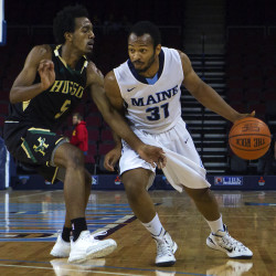 University of Maine's Troy Reid-Knight (right) drives the lane against Husson University's Trevon Butler during their exhibition game at the Cross Insurance Center in Bangor on Nov. 11, 2015.