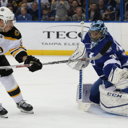Boston Bruins left wing Brad Marchand (left) shoots on goal as Tampa Bay Lightning goalie Ben Bishop, a former University of Maine standout, makes a save during the first period Tuesday night at Amalie Arena in Tampa, Florida.