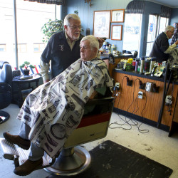 "Freeman Buzzell (left) gives Bob Hughgill a haircut Wednesday in his downtown Madison shop. Buzzell has been cutting hair in Madison since 1963 and believes the mill closure most likely will have a trickle-down effect on the community. ""Pretty much everyone thought that [the mill closing] wasn't going to happen that fast,"" said Buzzell."