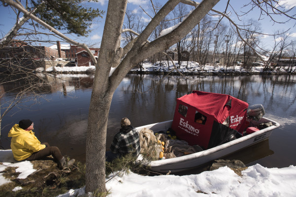 Fishermen wait on the bank of the Union River in Ellsworth on Tuesday morning. The elver fishing season officially started at noon, and people were staking out their spots for their nets.