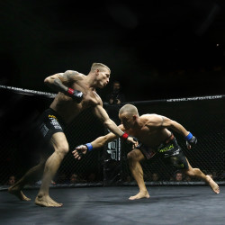 Windham native Jamie Harrison (right) reaches for a takedown attempt against Bruce Boyington of Brewer during their New England Fights XVII mixed martial arts main event at the Androscoggin Bank Colisee in Lewiston Saturday, April 11, 2015. Harrison won via first-round tapout with a rear-naked choke.