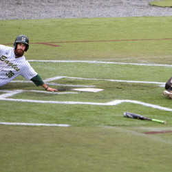 Husson University's Andrew Curran (left) slides safely into home past Thomas College's Alex Curtis during their baseball game at Husson in Bangor on Saturday.
