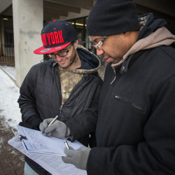 Ralph Tripp, 32, of Bangor and Maurice Gunn coordinate on a signature-gathering effort on a 2016 referendum for a York County casino outside the garage at Pickering Square in Bangor, Jan. 13, 2016.