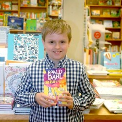 """Andrew Lyndaker holds a copy of """"Charlie and the Chocolate Factory"""" by Roald Dahl at Sherman's Maine Coast Book Shop in Damariscotta. He was delighted to find the book the day before going to New York to audition for the part of Charlie in a new Broadway musical based on the book."""