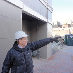 Dana Totman, president of Avesta Housing, points to apartment buildings along the skyline of Portland from the sidewalk alongside his organization's Oak Street Lofts project in this 2012 file photo.