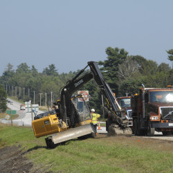 Maine Department of Transportation workers clear a ditch along the southbound lane of Route 202 in Hampden on Sept. 11, 2013.