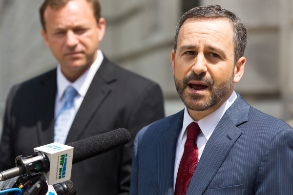 House Speaker Mark Eves (left) looks on as civil rights lawyer David Webbert addresses reporters during a press conference July 30, 2015, outside the U.S. District Court on Federal Street. The two filed a lawsuit against Gov. Paul LePage accusing him of blackmailing Good Will-Hinckley.