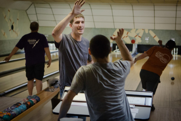 Brain Nappi (left) gets a high-five from Jordan Sparks after bowling a good candlepin frame on Monday night at Colonial Bowling Center in Westbrook. The bowling alley will close for good after a farewell tournament May 7.