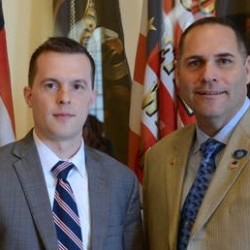 Jared Golden (left), D-Lewiston and Brad Farrin, R-Norridgewock, stand in the State House Hall of Flags on Thursday after a brief bill-signing ceremony with Gov. Paul LePage.