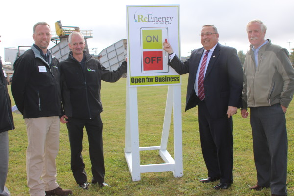 Gov. Paul LePage flips a switch symbolically marking the re-start of the ReEnergy biomass power plant on the Realty Road in Ashland in October 2014. Joining him are (from left) Mark Thibodeau, facility manager; an unidentified ReEnergy representative; and U.S. Sen. Angus King, I-Maine.
