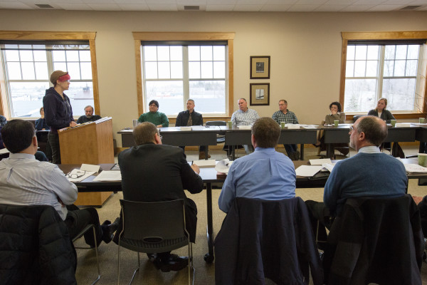 """Eddington planner Gretchen Heldmann (left, at podium) speaks out at the Bangor Area Comprehensive Transportation System's policy committee meeting on March 25. Heldmann opposes the planned connector."""""""