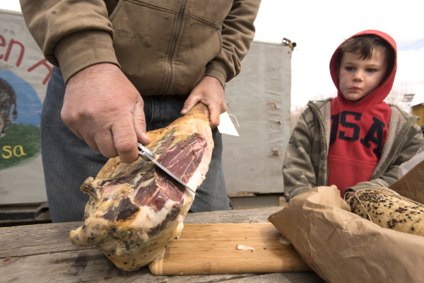 Four-year-old Frank Baker looks on as his father Mark Baker slices a piece of prosciutto for him while making a delivery stop at Ireland Hill Farm in Swanville. The Baker family raises mangalitsa pigs, that are prized for the quality of their meat at Bakers Green Acres farm in Marion, Michigan. Mark said he prepared the prosciutto in a traditional way.