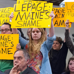 Carissa Tinker of Bar Harbor, a member of the Maine Student Action Network, center, along with over a dozen others, rose to her feet and pulled out signs during Wednesday night's town meeting at the Ramada Inn and Conference Center in Lewiston.