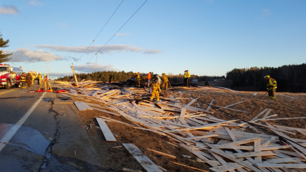 Lumber is scattered through a field along Route 17 in Washington following a crash that killed two people when a flatbed carrying the wood overturned onto three oncoming cars.