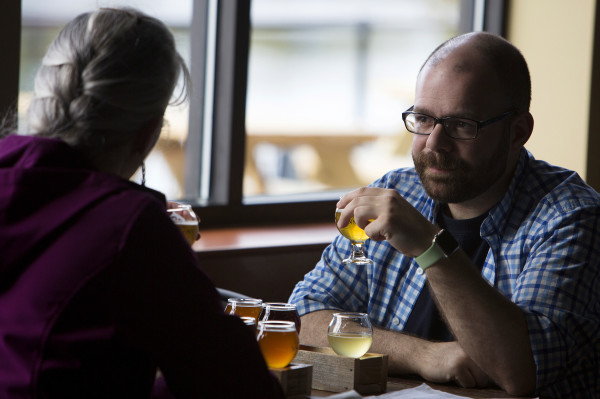 Jeremy Latour (right) enjoys a sampler of beers with Jae Hubbard at Mason's Brewing Co. in Brewer on Friday during the brewery's grand opening ceremony.