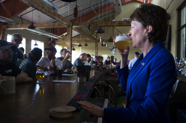 U.S. Sen. Susan Collins takes a sip of a beer she poured at Mason's Brewing Co. in Brewer on Friday during the brewery's grand opening ceremony.