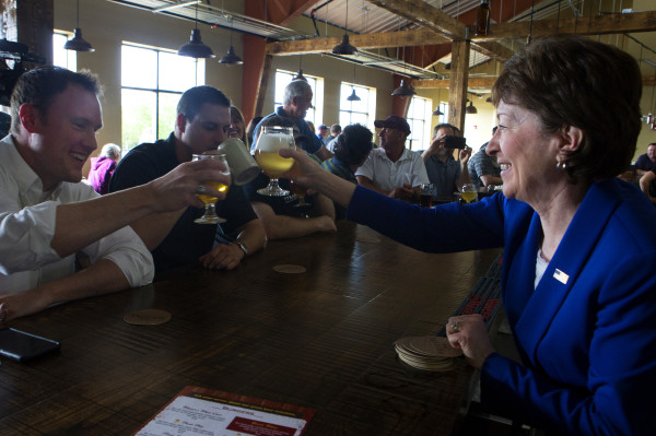 Brad Harris (left) cheers U.S. Sen. Susan Collins after Collins poured a beer at Mason's Brewing Co. in Brewer on Friday during the brewery's grand opening ceremony.
