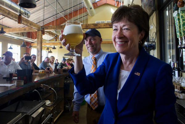 U.S. Sen. Susan Collins (right) holds up her beer she poured at Mason's Brewing Co. in Brewer on Friday with owner Christopher Morley during the brewery's grand opening ceremony.
