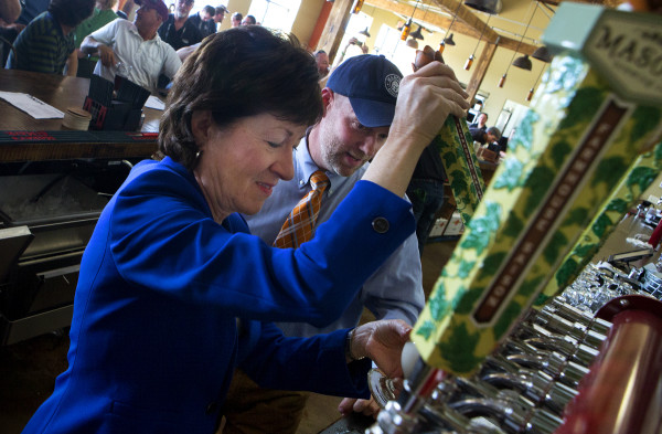 U.S. Sen. Susan Collins (left) pours a beer at Mason's Brewing Co. in Brewer on Friday while owner Christopher Morley watches during the brewery's grand opening ceremony.