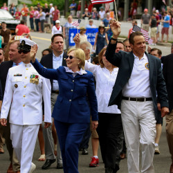 Democratic U.S. presidential candidate Hillary Clinton (C) waves to the crowd as she takes part in the Memorial Day parade with New York State Governor Andrew Cuomo (R) in Chappaqua, New York, U.S. May 30, 2016.