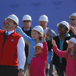 Karl Ward, president and CEO of Nickerson & O'Day Inc., and Brewer school students from kindergarten through eighth grade direct a crane operator to raise the last steel beam on the Brewer Elementary-Middle School campus construction project during a ceremony involving the students, Brewer leaders and contractors on Nov. 12, 2009.
