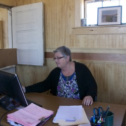 Sharon Mack, executive director of the Machias Bay Area Chamber of Commerce, works in her new office at the train station. The chamber moved from Main Street to the train station May 5-6.