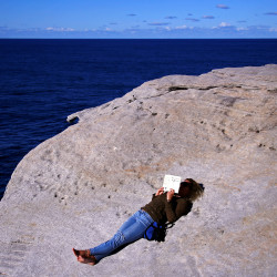 A woman reads a book as she lies on a cliff on a sunny day in Sydney, Australia, May 29, 2016.