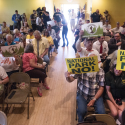 People display signs both supporting and opposing the proposed national monument before a congressional field hearing on Wednesday in East Millinocket.