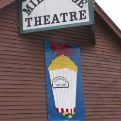 A sign showing a container of popcorn has been created to represent the success of fundraising efforts for the Milbridge Theatre. The red lines at the bottom of the container indicate almost $10,000 has been raised toward a goal of $60,000, the amount needed to purchase the building.