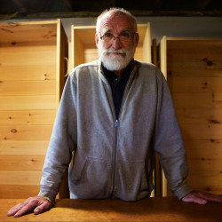 """Chuck Lakin of Waterville stands in his basement with a selection of wooden coffins he made on site. Lakin, a retired reference librarian, also teaches others how to build their own coffins and lectures about """"natural burials."""""""