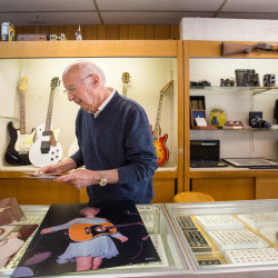Bangor native Orlando Frati, 84, shows off some of the photographs he has taken over the years on Wednesday at his pawn shop on State Street in Bangor.