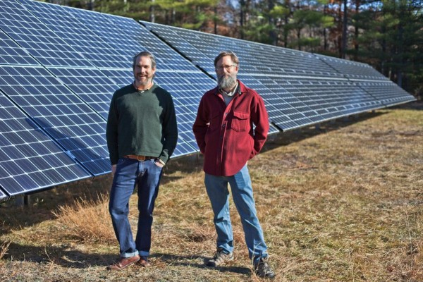 Aaron Anker (left) and Nat Peirce, owners of GrandyOats, stand in front of 288 solar panels in this file photo.
