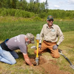 Mike Roukas (left) of East Machias and Jim Sparaga of Marshfield work to dig out parts of the airport runway lights that need to be replaced. They were part of a volunteer crew working Saturday.