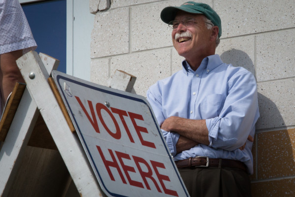 Dr. Charles Radis talks to voters outside the East End Community School in Portland on Tuesday.