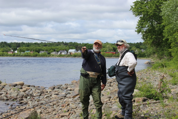 Denis Dauphinee (left) and Pete Douvarjo scope out likely shad-fishing spots on June 10 on the Penobscot River in Old Town.
