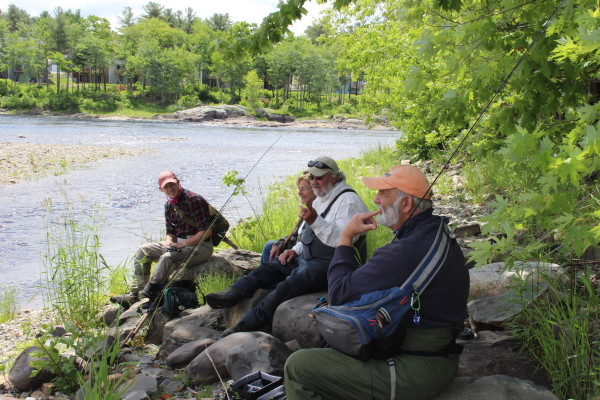 From left, Hazen Dauphinee, Sandy Douvarjo, Pete Douvarjo and Denis Dauphinee relax on some rocks after fishing for shad in the Penobscot River on June 10 in Old Town.